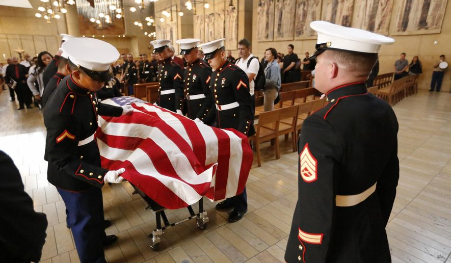 Marine pallbearers prepare the flag-draped coffin with the remains of Lance Corporal Carlos A. Segovia-Lopez, the 19-year-old Marine from Camp Pendleton who died on Sept. 19 after he was shot in South Los Angeles, during a funeral service Wednesday, Oct. 5, 2016, at the Cathedral of Our Lady of the Angles in Los Angeles. Segovia was in LA on weekend leave from Camp Pendleton, and was on his way to a family friend's home for the night when someone may have walked up to his car or shot from another vehicle. (Al Seib / Los Angeles Times viaAP, Pool)
