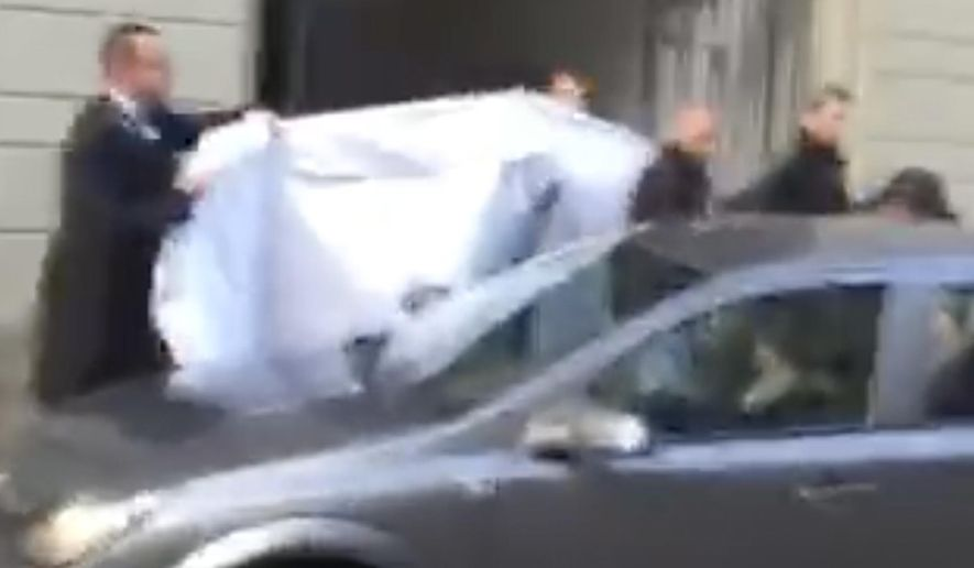 FILE- In this Wednesday, May 27, 2015 file picture taken from a cell phone video, hotel employees hold a blanket to hide the identity of a person led out of a side entrance of the Baur au Lac hotel to a waiting car in Zurich, Switzerland. FIFA is no longer hosting its executives at the waterside super-luxurious, lake-side hotel where Swiss police launched dawn raids last year. (AP Photo/Rob Harris, File)