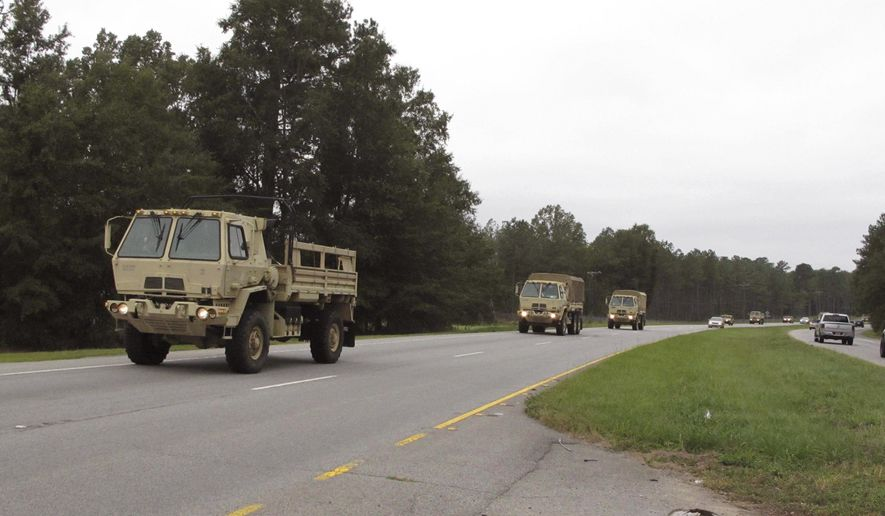 South Carolina National Guard vehicles head east on U.S. Highway 378 after leaving their headquarters on Wednesday, Oct. 5, 2016, near Columbia, S.C. Guard units are helping with traffic and other preparations for Hurricane Matthew. South Carolina authorities are preparing to evacuate more than 1 million people,  or about a quarter of the state's population, from low-lying coastal areas as Hurricane Matthew threatens.  (AP Photo/Jeffrey Collins)
