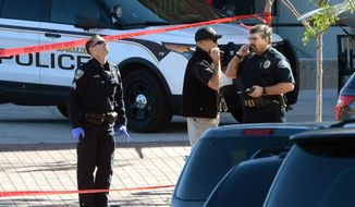 Emergency personnel and police officers work the scene of an officer involved shooting near the Champions Center on the University of Colorado Boulder, Colo., campus Wednesday, Oct. 5, 2016. A man armed with a machete was shot and killed by police Wednesday at the university after officials say he refused to drop the knife. (Paul Aiken/Daily Camera via AP)