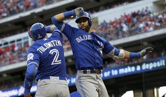 Toronto Blue Jays' Troy Tulowitzki (2) and Jose Bautista celebrate Bautista's three-run home run against the Texas Rangers during the ninth inning of Game 1 of baseball's American League Division Series, Thursday, Oct. 6, 2016, in Arlington, Texas. The Blue Jays won 10-1. (AP Photo/LM Otero)