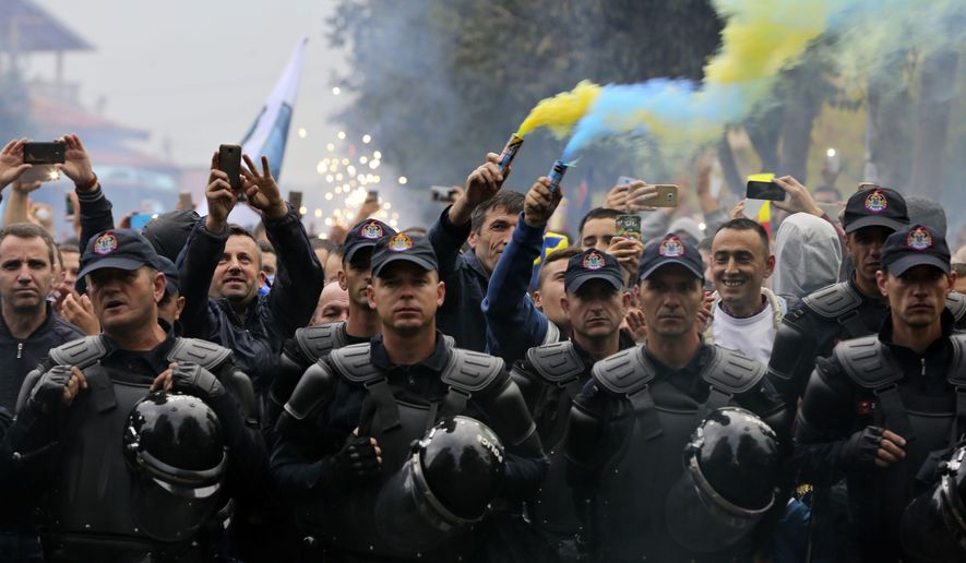 "Members of ""Dardanet"", a Kosovo fan club, are escorted by police as they celebrate the group's arrival, before the World Cup Group I qualifying soccer match between Croatia and Kosovo in Shkoder, Albania, Thursday Oct. 6, 2016. (AP Photo/Visar Kryeziu)"