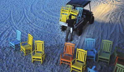 Workers start before dawn removing umbrellas and the colorful rocking chairs that line the Cocoa Beach Pier, moving them to a safer location as Hurricane Matthew approaches, Wednesday, Oct. 5, 2016, in Cocoa Beach, Fla. (Malcolm Denemark/Florida Today via AP)