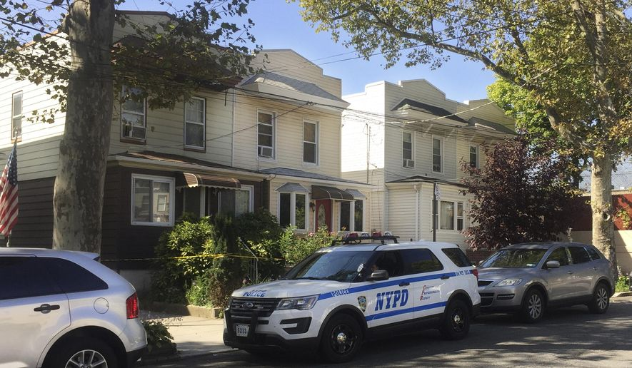 A police vehicle sits in front of a house, left, where officers conducting a welfare check discovered the decomposing body of Erika Kraus-Breslin, the 85-year-old grandmother of Christopher Fuhrer, 30, who lived in the house with her in the Queens borough of New York, Thursday, Oct. 6, 2016. Fuhrer, fearful he'd become homeless after the death of his doting grandmother five months ago, kept her corpse wrapped in plastic bags inside her house, masking the smell with air fresheners and a fan, police said after arresting him on improper burial and other charges. (AP Photo/Mike Balsamo)