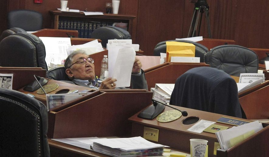 File - This April 17, 2016, file photo shows Alaska state Rep. Benjamin Nageak, D-Barrow, reclining with some reading material during a break in a floor session at the Legislature in Juneau, Alaska. A state court judge found errors in how the primary election was conducted in a northern Alaska legislative election, awarding the race to Nageak over challenger Dean Westlake. (AP File Photo/Becky Bohrer, File)