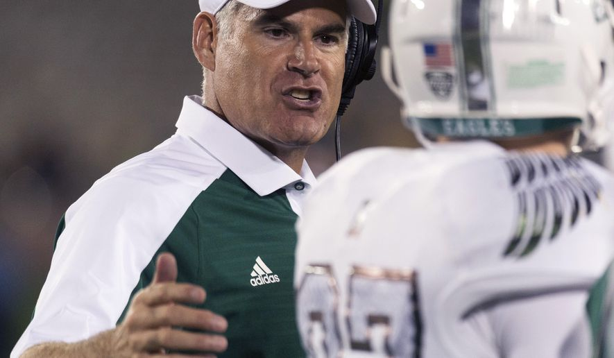 FILE- In this Sept. 10, 2016, file photo, Eastern Michigan head coach Chris Creighton, left, talks to wide receiver Mathew Sexton during the third quarter of an NCAA college football game against Missouri, in Columbia, Mo. After a turbulent offseason in which the school hierarchy had to reaffirm its commitment to playing Division I football at all, Eastern Michigan is off to its best start since 1995. The Eagles improved to 4-1 last weekend with a win over defending MAC champion Bowling Green. (AP Photo/L.G. Patterson, File)