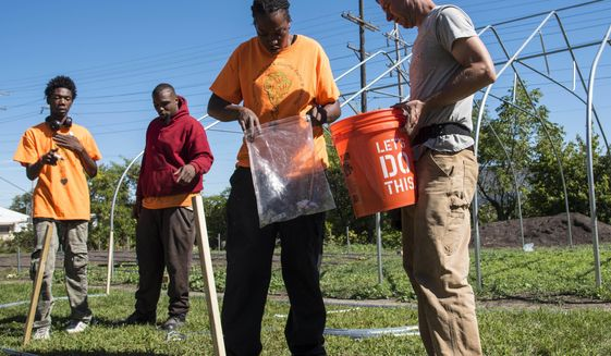 ADVANCE FOR USE SATURDAY, OCT. 8, 2016 AND THEREAFTER - In this  Sept. 27, 2016 photo, Adam Montri, right, a hoophouse outreach specialist from Michigan State University talks with residents of Blackhawk Court as they assemble one of the two hoop houses going up at Blackhawk Courts Farm in in Rockford, Ill. The 70- by 30-foot hoop houses are greenhouse structures consisting of PVC pipe and a polyethylene cover. The houses will supplement the existing farm, increasing the growing season from 10 weeks to 40. (Kayli Plotner/Rockford Register Star via AP)