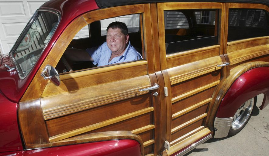In this Sept. 14, 2016 photo, Randy Goodrich sits in his 1948 Pontiac Woody  Wagon that is made of approximately 50% wood at his home in Decatur, Ill. Goodrich said that 68 years ago, Pontiac didn't actually make a station wagon. They built an already magnificent Silver Streak sedan and then shipped very few of them off to the Ionia Mfg. Co. in Michigan, which did the station wagon bodywork in wood. (Jim Bowling/Herald & Review via AP)  /Herald & Review via AP)