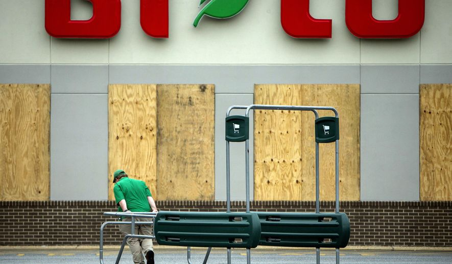 Josh Sweat, a butcher at the BiLo grocery store, moves a shopping cart return rack during storm preparations for Hurricane Matthew, Thursday, Oct. 6, 2016, in Darien, Ga.  The hurricane picked up steam as it closed in, growing from a Category 3 to a Category 4 storm by late morning.  (AP Photo/Stephen B. Morton)