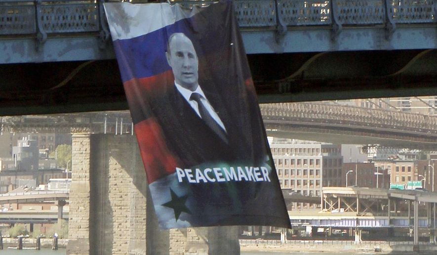"In this photo provided by Gothamist.com, a banner bearing an image of Russian President Vladimir Putin showing him with a Russian and Syrian flag as backdrop and labeling him a ""peacemaker"" hangs from the Manhattan Bridge, Thursday, Oct. 6, 2016, in New York.  Witnesses told the New York Post they saw two people unfurl the banner at about 1:45 p.m. Thursday. Police say officers removed the banner about an hour later. No arrests have been made, but investigation is continuing according to police. (Nathan Tempey/Gothamist.com via AP)"