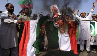 Supporters of Pakistan Tehreek-e-Insaf party burn the representation of Indian flags during a protest in Peshawar, Pakistan, Wednesday, Oct. 5, 2016. Officials in Islamabad say Pakistan and India are trying to de-escalate border tensions after their troops exchanged several rounds of gunfire over the last week in the disputed Kashmir region. (AP Photo/Mohammad Sajjad)