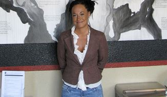FILE - In this July 24, 2009, file photo, Rachel Dolezal, a leader of the Human Rights Education Institute, stands in front of a mural she painted at the institute's offices in Coeur d'Alene, Idaho. Dolezal, the former NAACP chapter president who made headlines in 2015 when her race came into question, has been tapped to speak at a Martin Luther King Day celebration set for January in Cary, N.C. (AP Photo/Nicholas K. Geranios, File)