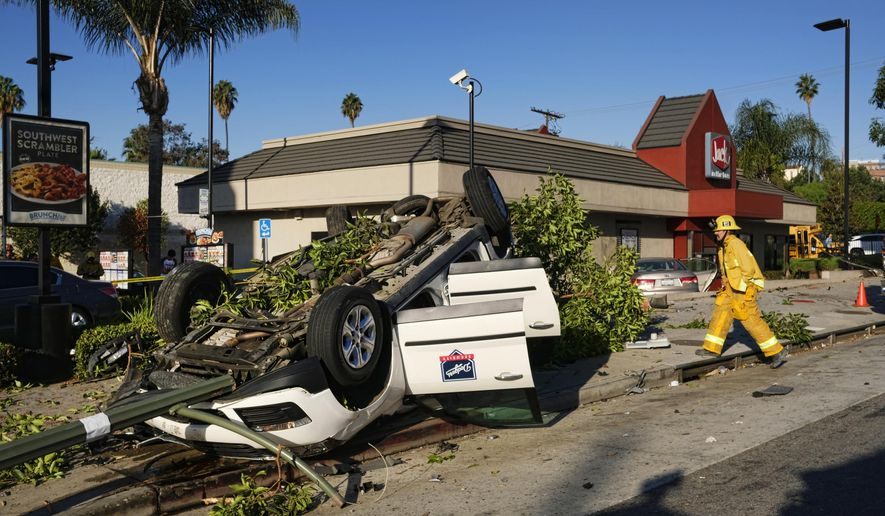 Los Angeles fire department firefighters arrive at the scene of a car crash in front of a fast food restaurant near downtown Los Angeles on Thursday, Oct. 6, 2016. The traffic accident left a vehicle overturned on a sidewalk and another smashed-up car in the drive-thru lane of a fast-food restaurant. (AP Photo/Richard Vogel)