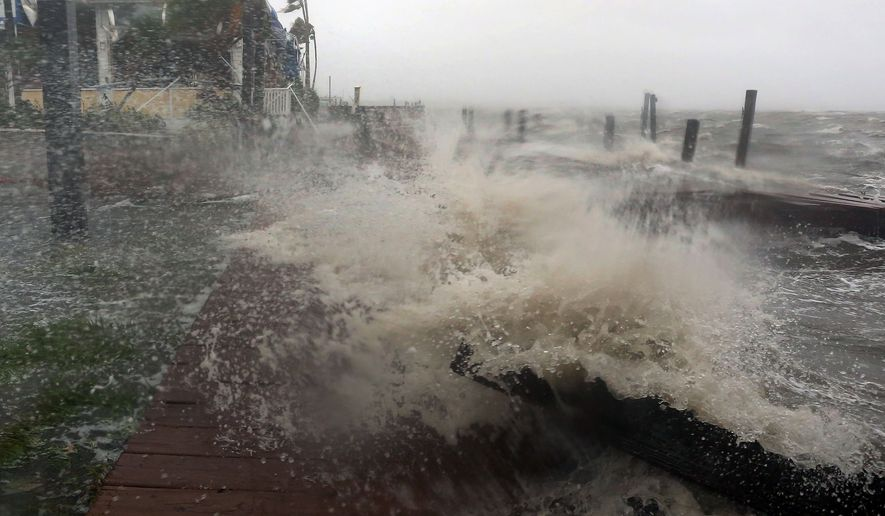Surf from the Banana River crashes up on a dock at Sunset Grill in Cocoa Beach, Fla., as Hurricane Matthew hits Florida's east coast, Friday, Oct. 7, 2016. (Red Huber/Orlando Sentinel via AP)