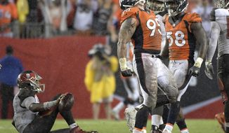 "FILE - In this Oct. 2, 2016, file photo, Denver Broncos defensive end Derek Wolfe (95) celebrates after sacking Tampa Bay Buccaneers quarterback Jameis Winston, left, during an NFL football game in Tampa, Fla. Wolfe is the unsung member of Denver's dazzling defense, the ""guy who does all the dirty work,"" as Chris Harris Jr. said. In his last 14 games, Wolfe has a dozen sacks, an impressive number for an interior lineman. (AP Photo/Phelan M. Ebenhack, File)"