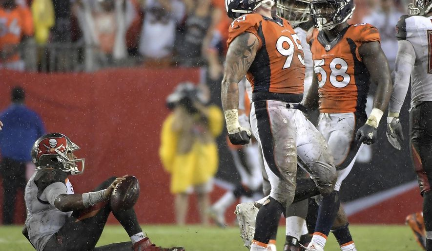 """FILE - In this Oct. 2, 2016, file photo, Denver Broncos defensive end Derek Wolfe (95) celebrates after sacking Tampa Bay Buccaneers quarterback Jameis Winston, left, during an NFL football game in Tampa, Fla. Wolfe is the unsung member of Denver's dazzling defense, the """"guy who does all the dirty work,"""" as Chris Harris Jr. said. In his last 14 games, Wolfe has a dozen sacks, an impressive number for an interior lineman. (AP Photo/Phelan M. Ebenhack, File)"""