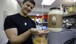 "FILE - In this Dec. 3, 2013, file photo, Hampton Creek Foods CEO Josh Tetrick holds a species of yellow pea used to make Just Mayo, a plant-based mayonnaise, in San Francisco. On Thursday, Oct. 6, 2016, the U.S. Department of Agriculture said that an egg industry group's discussions about thwarting the sale of an eggless vegan spread were inappropriate. The investigation also determined that the American Egg Board, which is responsible for the ""Incredible, Edible Egg"" slogan, should not have paid for pro-egg ads to appear online when people searched for Hampton Creek's Just Mayo. (AP Photo/Eric Risberg, File)"