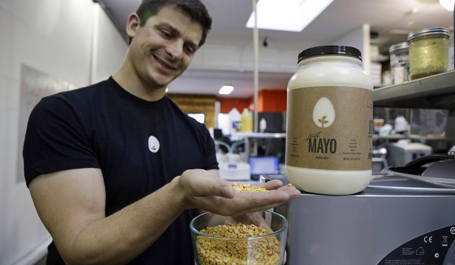 """FILE - In this Dec. 3, 2013, file photo, Hampton Creek Foods CEO Josh Tetrick holds a species of yellow pea used to make Just Mayo, a plant-based mayonnaise, in San Francisco. On Thursday, Oct. 6, 2016, the U.S. Department of Agriculture said that an egg industry group's discussions about thwarting the sale of an eggless vegan spread were inappropriate. The investigation also determined that the American Egg Board, which is responsible for the """"Incredible, Edible Egg"""" slogan, should not have paid for pro-egg ads to appear online when people searched for Hampton Creek's Just Mayo. (AP Photo/Eric Risberg, File)"""