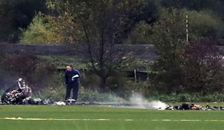 """An investigator looks over the scene where a helicopter crashed in a field   in Lino Lakes, Minn., on Thursday, Oct. 6, 2016.  Two people died when a helicopter erupted in """"a large fireball"""" as it crashed into a field in the Twin Cities suburb, a sheriff's official said Friday. (Richard Tsong-Taatarii/Star Tribune via AP)"""