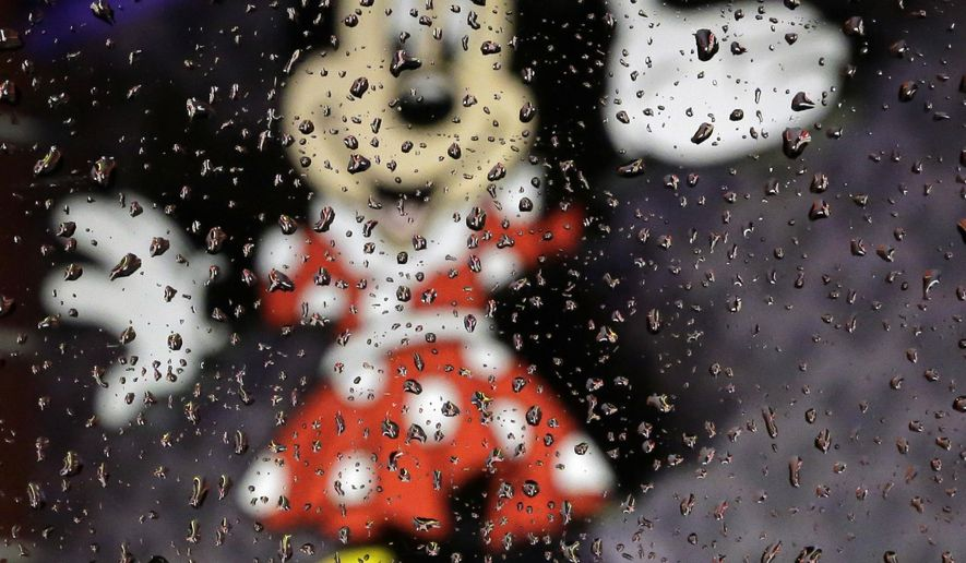 Rain clings to a window near a Minnie Mouse sign near Walt Disney World, Thursday, Oct. 6, 2016, in Orlando, Fla. Three of the world's most popular tourist attractions, Universal Studios, Walt Disney World and SeaWorld all made a rare decision to close their theme parks Thursday ahead of Hurricane Matthew's arrival. (AP Photo/Eric Gay)