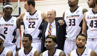 Illinois coach John Groce, center top, stands between Maverick Morgan (22) and Mike Thorne Jr. (33), during a team photo at an NCAA college basketball media day in Champaign, Ill., Friday, Oct. 7, 2016. (John Dixon/News-Gazette via AP)