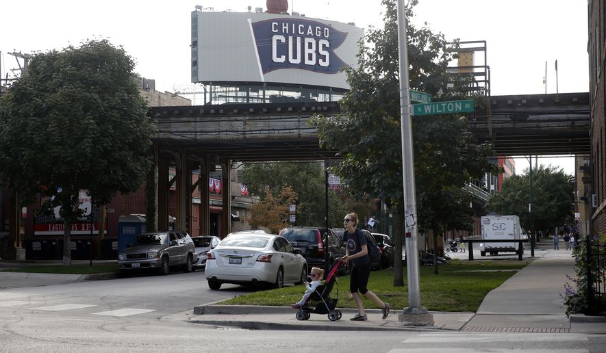 A woman pushes a stroller with a toddler by Wrigley Field, Wednesday, Oct. 5, 2016, in Chicago. Living near the workplace is one of the unique attractions of playing in a vibrant residential neighborhood like Wrigleyville. For the players and staff who take advantage, it means almost nonexistent commutes, more time with family and a chance to mingle with the surroundings in a way that might not be possible in other cities. For residents, well, you might have a Cub living next door. (AP Photo/Kiichiro Sato)