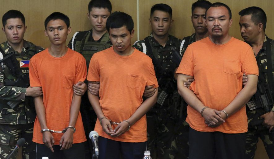 Suspected Muslim extremists, from left in front row, Wendel Apostol Facturan, Musali Mustapha and TJ Tagdaya Macabalang are presented to reporters at Camp Aguinaldo military headquarters in Quezon city, north of Manila, Philippines Friday, Oct. 7, 2016. Philippine troops have captured the three suspects in the bombing of a night market that killed 15 people and seized a cellphone video of the blast from them that they apparently took for propaganda purposes, the defense chief said Friday. (AP Photo/Aaron Favila)