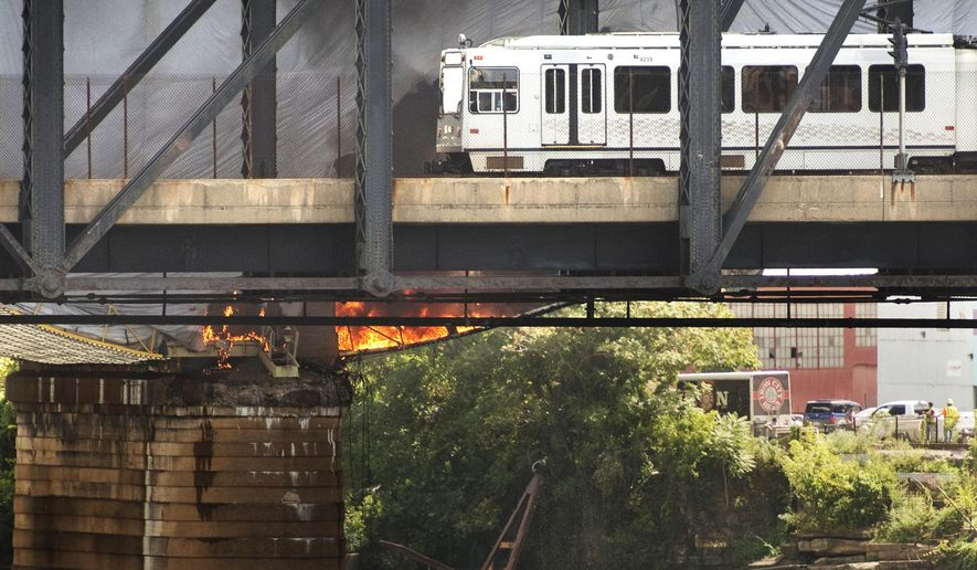 In this Sept. 2, 2016 photo, a light rail train on its way downtown pauses as it passes a tarp fire on the nearby Liberty Bridge in Pittsburgh. A contractor didn't obtain a key safety permit before welding caused plastic pipe and a construction tarp to burn on the Liberty Bridge last month, resulting in a 24-day shutdown of a primary artery into downtown Pittsburgh, the city's fire chief said. (Steve Mellon/Pittsburgh Post-Gazette via AP)
