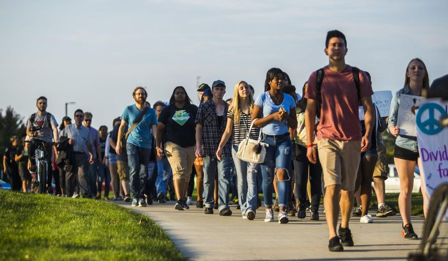 In this Thursday, Oct. 6, 2016 photo, Eastern Michigan students march in a silent protest on campus in Ypsilanti, Mich., in response to racist graffiti found last month on campus. (Katy Kildee/The Ann Arbor News via AP)