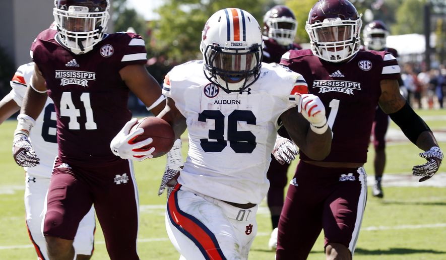 Auburn running back Kamryn Pettway (36) runs past Mississippi State defensive backs Mark McLaurin (41) and Brandon Bryant (1) for a first down in the first half of an NCAA college football game , Saturday, Oct. 8, 2016, in Starkville, Miss.  (AP Photo/Rogelio V. Solis)