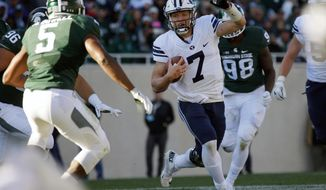 BYU quarterback Tayson Hill (7) scrambles against Michigan State's Andrew Dowell (5) during the second quarter of an NCAA college football game, Saturday, Oct. 8, 2016, in East Lansing, Mich. (AP Photo/Al Goldis)