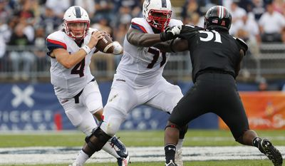 Connecticut quarterback Bryant Shirreffs runs behind the block of offensive lineman Richard Levy during the first half of an NCAA college football game against Cincinnati Saturday, Oct. 8, 2016, in East Hartford, Conn. (AP Photo/Winslow Townson)