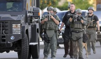 FILE - In this Dec. 2, 2015, file photo, authorities search an area following a shooting that killed several people at a social services center in San Bernardino, Calif. California voters are considering expanding some of the nation's toughest gun control measures nearly a year after the terrorist shootings in San Bernardino. Proposition 63 on the November 2016 ballot would outlaw possession of large-capacity ammunition magazines, require permits to buy ammunition and extend California's unique program that allows authorities to seize firearms from owners who bought guns legally but are no longer allowed to own them. (James Quigg/The Daily Press via AP)
