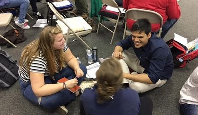 In this Wednesday, Sept. 17, 2016 photo, Anil Yadav, one the political professionals from India participating in the University of Akron's new International Campaign Fellows program, speaks with other volunteers at a campaign field office in Columbus, Ohio. Fellows from India, Liberia and Brazil are taking and sharing lessons on U.S. battleground politics and grassroots campaigning through the program this fall. (University of Akron ICF Program via AP)