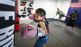 ADVANCE FOR SATURDAY OCT. 8 AND THEREAFTER - In a Wednesday, Sept.26, 2016 photo, Marissa Solis punches a bag as her brother David, far right, works out with John DeVall  out at DeVall MMA & BJJ in Sioux City, Iowa. Siblings Marissa, Jazlynn, David and Eddie Solis train in mixed martial arts at DeVall MMA & BJJ. Marissa is a Liberty Elementary School fifth grader who enjoys hanging out with her friends and playing with her dog Bullet when she isn't practicing MMA.  (Jim Lee/Sioux City Journal via AP)