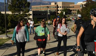 In this Sept. 28, 2016 photo, Nick Harmon, 24, center who has Down Syndrome, walks through campus at University of Colorado Colorado Springs,  Colo.   The legislature this year passed a law that allows people with intellectual disabilities, including Down Syndrome, to enroll in college even if they don't have the SAT or ACT scores or high school courses to gain admittance.  (RJ Sangosti/The Denver Post via AP)