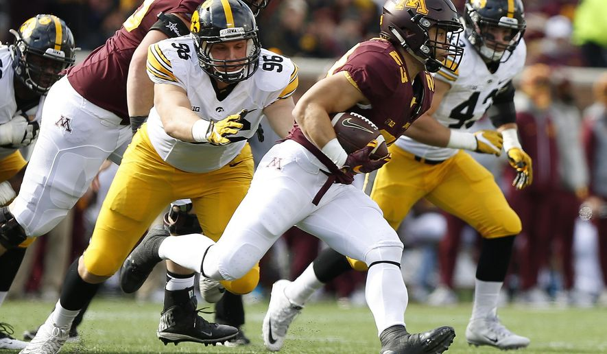 Minnesota running back Shannon Brooks (23) runs out of reach of Iowa defensive end Matt Nelson (96) during an NCAA college football game Saturday, Oct. 8, 2016, in Minneapolis. (AP Photo/Stacy Bengs)