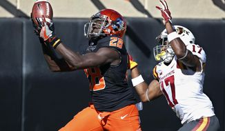 Oklahoma State wide receiver James Washington (28) catches a pass in front of Iowa State defensive back Jomal Wiltz (17) in the second quarter of an NCAA college football game in Stillwater, Okla., Saturday, Oct. 8, 2016. (AP Photo/Sue Ogrocki)