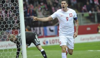 Poland's Robert Lewandowski celebrates after scoring a goal as Denmark's goalkeeper Kasper Schmeichel, left, picks the ball  during their World Cup Group E qualifying soccer match at the National Stadium in Warsaw, Poland, Saturday, Oct. 8, 2016. (AP Photo/Alik Keplicz)
