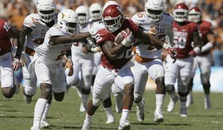 Oklahoma running back Samaje Perine (32) runs against Texas cornerback Kris Boyd (2) during the first half of an NCAA college football game in Dallas Saturday, Oct. 8, 2016. (AP Photo/LM Otero)