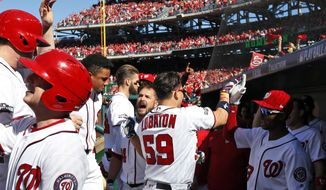 Washington Nationals' Jose Lobaton (59) and others, celebrate his three-run homer during the fourth inning of Game 2 of baseball's National League Division Series against the Los Angeles Dodgers at Nationals Park, Sunday, Oct. 9, 2016, in Washington. (AP Photo/Alex Brandon)