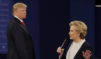 Donald Trump listens to Hillary Clinton during the second presidential debate at Washington University in St. Louis on Sunday. (Associated Press)