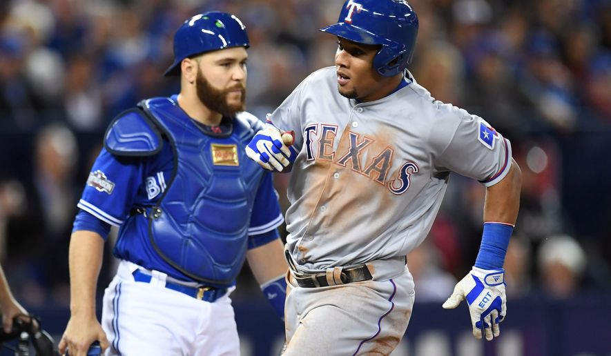 Texas Rangers' Carlos Gomez (14) scores a run past Toronto Blue Jays' catcher Russell Martin during first inning game three American League Division Series baseball action in Toronto on Sunday, Oct. 9, 2016. (Nathan Denette/The Canadian Press via AP)