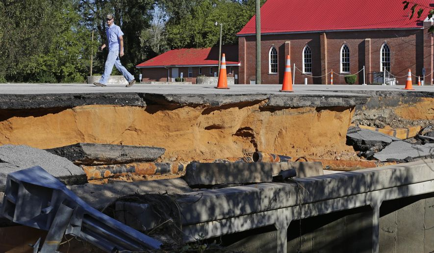 A man walks across a road damaged by floodwaters caused by rain from Hurricane Matthew in Fayetteville, N.C., Sunday, Oct. 9, 2016.  Hurricane Matthew's torrential rains triggered severe flooding in North Carolina on Sunday as the deteriorating storm made its exit to the sea, and thousands of people had to be rescued from their homes and cars. (AP Photo/Chuck Burton)