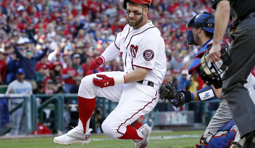 Washington Nationals' Bryce Harper, left, is tagged out at home by Los Angeles Dodgers catcher Yasmani Grandal (9) after a sacrifice fly-attempt by teammate Anthony Rendon in the fifth inning during Game 2 of baseball's National League Division Series against the Los Angeles Dodgers at Nationals Park, Sunday, Oct. 9, 2016, in Washington. (AP Photo/Alex Brandon)