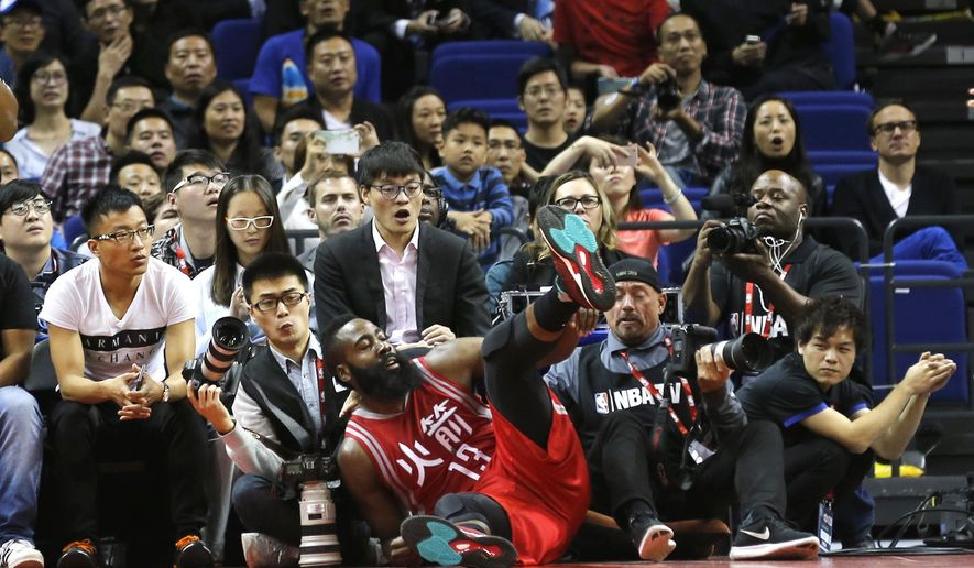 Houston Rockets James Harden falls into the crowd during their preseason NBA game against the New Orleans Pelicans in Shanghai, China, Sunday, October, 9, 2016. (AP Photo)