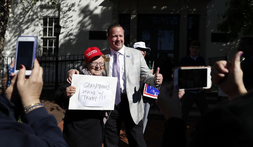 """Corey Stewart, chairman of Republican presidential candidate Donald Trump's Virginia campaign, right, gives the thumbs-up as he poses for a photo with Trump supporter Heidi Saba with her sign that reads """"Grandmothers Stand w/Trump!!!"""" outside the Republican National Committee Headquarters in Washington, Monday, Oct. 10, 2016. Stewart and Virginia Women for Trump gathered in support of Trump.  (AP Photo/Carolyn Kaster)"""