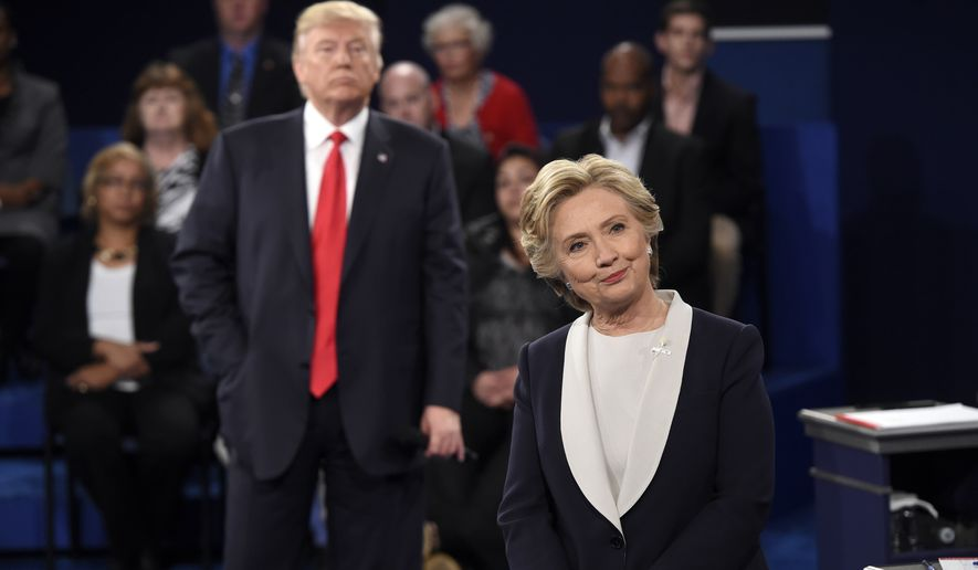 Democratic presidential nominee Hillary Clinton, right, and Republican presidential nominee Donald Trump listen to a question during the second presidential debate at Washington University in St. Louis, Sunday, Oct. 9, 2016. (Saul Loeb/Pool via AP)