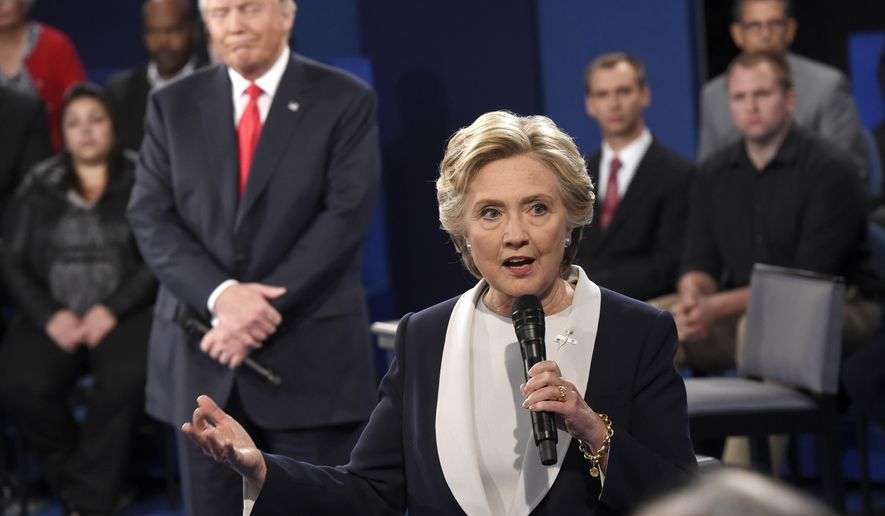 Democratic presidential nominee Hillary Clinton speaks as Republican presidential nominee Donald Trump reacts during the second presidential debate at Washington University in St. Louis, Sunday, Oct. 9, 2016. (Saul Loeb/Pool via AP)