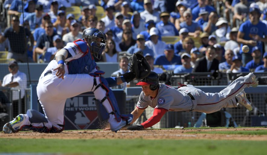 Washington Nationals' Trea Turner, right, scores past Los Angeles Dodgers catcher Yasmani Grandal on a double by Jayson Werth during the second inning in Game 3 of baseball's National League Division Series in Los Angeles, Monday, Oct. 10, 2016. (AP Photo/Mark J. Terrill)